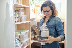 Middle-aged woman picking food from storage cabinet in kitchen. Storage with wooden shelves royalty free stock image