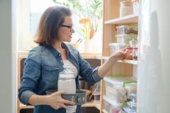 Middle-aged woman picking food from storage cabinet in kitchen. Storage with wooden shelves royalty free stock photo