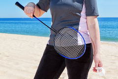 Middle-aged woman playing badminton on the beach. Royalty Free Stock Images
