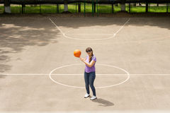 Middle aged woman playing a game of basketball Stock Photos