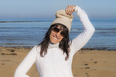 Middle-aged woman playing with her woolen cap at the beach Stock Photos