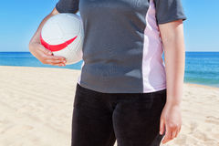 Middle-aged woman playing volleyball at the beach. Stock Images
