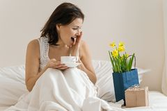 Middle aged woman is pleased with gift, bouquet of flowers, sitting in morning in bed with cup of coffee. Emotion of happiness, stock photos