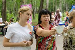 Middle-aged woman plus size measures with body fat monitor in her hands under guidance of young female volunteer. Komsomolsk-on-Amur, Russia - August 19, 2018 stock image