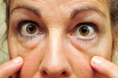 Middle Aged Woman Pointing at her eyes closeup Stock Image