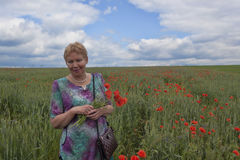 Middle-aged woman on a poppy field Royalty Free Stock Photo