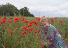A middle-aged woman on a poppy field Stock Photos