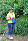 Middle-aged woman posing with a watering can Stock Photography