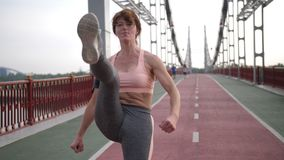 Middle-aged woman practicing karate in city. Attractive middle-aged redhed woman with slim, fit sporty body practiving karate on city bridge. Healthy female stock video