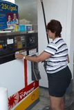 Middle aged woman prepares to purchase gasoline. At a gas station in Belleville, Michigan royalty free stock images