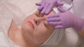 Middle-aged woman on the procedure in the cosmetology center. Close-up. The hands of a cosmetologist in lilac gloves put. A soap solution on the female face stock video