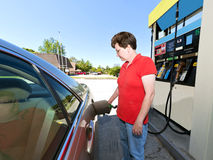 Middle Aged Woman Pumping Gas At Station. Middle-aged woman refuels her car at station Stock Photos
