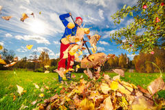 Middle aged woman raking leaves. In bright sunny autumn day Royalty Free Stock Photo