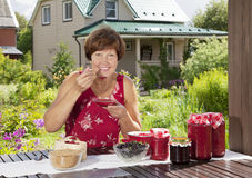 Middle aged woman with raspberry jam Royalty Free Stock Photography