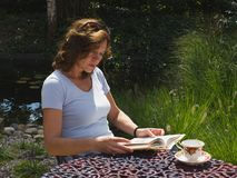 A middle-aged woman reading book with concentration in the garden. A middle-aged woman reading book with concentration in the garden with pool, summer, sunny royalty free stock photo