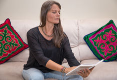 Middle aged woman reading a book. Stock Photos