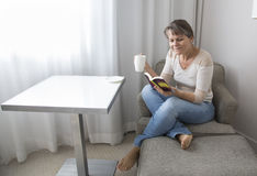 Middle aged woman reading a book and drinking coffee Stock Photos