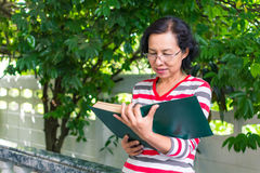 Middle-aged woman reading a book at home stock photos
