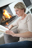 Middle-aged woman reading book at home Royalty Free Stock Photography