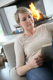 Middle-aged woman reading book at home Stock Image