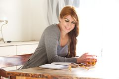 Middle aged woman reading a book at home. Portrait of attractive middle aged woman sitting at table with tea and reading book Stock Photo