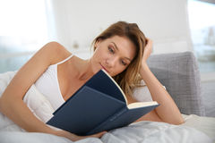 Middle-aged woman reading book on sofa Stock Images