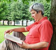 Middle-aged woman reading book by tree Royalty Free Stock Photography