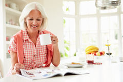 Middle Aged Woman Reading Magazine Over Breakfast. Whilst Holding Hot Drink Sitting Down royalty free stock photography