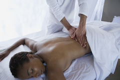 Middle Aged Woman Receiving Back Massage. An African American middle aged women receiving back massage at spa royalty free stock images