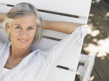 Middle Aged Woman Reclining On Sunlounger. Closeup of a smiling middle aged woman reclining on sunlounger Stock Photography