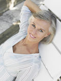 Middle Aged Woman Reclining On Sunlounger. Elevated view of a smiling middle aged woman reclining on sunlounger Stock Image