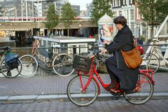 A middle-aged woman on a red bicycle. Amsterdam, Netherlands. A woman on a red bicycle in the historical center. Eenhoornsluis bridge over the Princengrach canal royalty free stock photo