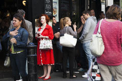 Middle-aged woman in a red dress drinking beer in the crowd outside the pub. LONDON, UK - APRIL 22, 2016: Middle-aged woman in a red dress drinking beer in the royalty free stock photo