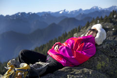 Middle-Aged Woman Relaxes in Warm Winter Sunshine  at 1st Peak on Mount Seymour, BC Canada. Dressed in Colourful Jacket. Middle-Aged Chinese-Canadian woman hiker Stock Photos