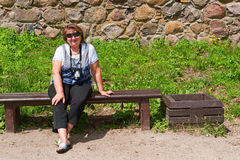 Middle-aged woman relaxing on a bench Stock Image
