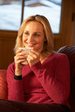 Middle Aged Woman Relaxing With Hot Drink On Sofa Royalty Free Stock Photography