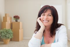 Middle Aged Woman Relaxing Inside Empty Room With Moving Boxes stock photography