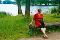 Middle-aged woman relaxing by the lake Royalty Free Stock Images