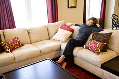 Middle-aged woman relaxing on living room sofa Stock Image