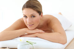 Middle-aged woman relaxing on massage bed Stock Photography