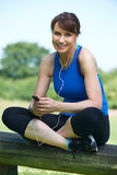 Middle Aged Woman Relaxing With MP3 Player After Exercise Stock Photography
