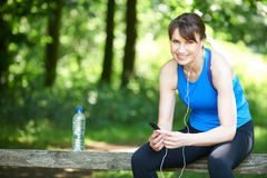 Middle Aged Woman Relaxing With MP3 Player After Exercise Stock Images