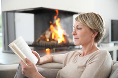 Middle-aged woman relaxing on the sofa reading book Stock Images