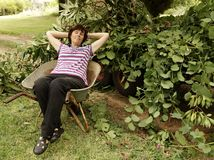 Middle-aged Woman Relaxing In Wheelbarrow. A middle-aged woman relaxes in her wheelbarrow after collecting cuttings in her garden Royalty Free Stock Images