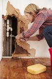 Middle aged woman repairing burst water pipe, vertical stock photo