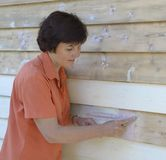 Middle-aged Woman Repairing Weatherboards with Putty. Stock Photos