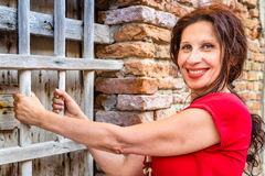 Middle-aged woman rests on wooden grates. Middle-aged woman playfully rests on wooden grates of a window in a town  in Northern Italy Stock Image