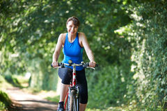 Middle Aged Woman Riding Bike Through Countryside Royalty Free Stock Photos
