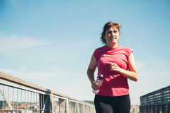 Middle aged woman running with water bottle. Middle aged woman running with a water bottle in hand in a sunny and hot day Stock Photo
