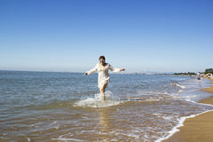 Middle-aged woman runs on water by the sea. Middle-aged woman in a white dress running on water against the sea on a sunny day Royalty Free Stock Image